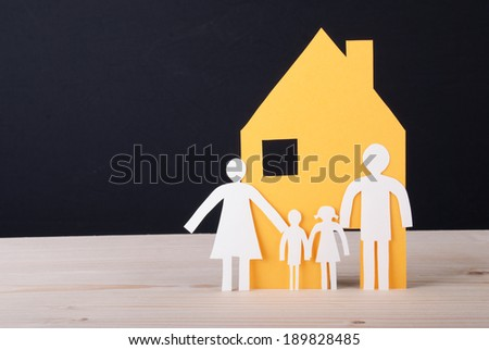 A Yellow House with a White Paper Chain Family - stock photo