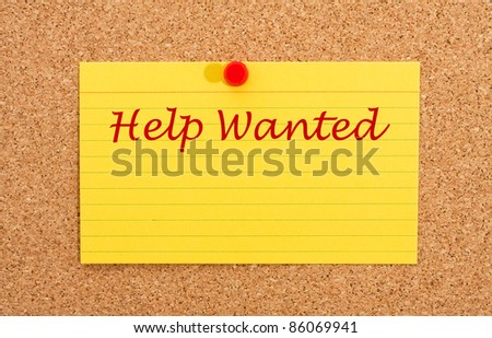 A yellow index card on a cork board with the words help wanted on it - stock photo
