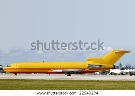 A yellow jet airplane taxiing prior to departure.