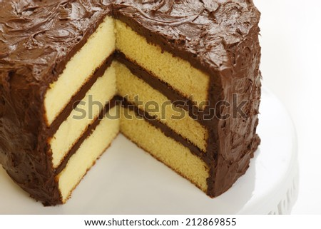 yellow layer cake with chocolate icing with a slice missing - stock ...