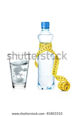 A yellow measure tape wrapped around a bottle and glass of water isolated on white background - stock photo