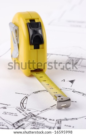 A yellow measuring tape on a technical drawing with selective focus - stock photo