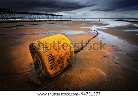 a yellow mooring buoy lying in the sand on the beach waiting for the tide to come in. A moody image with the pier and a threatening sky in the background.