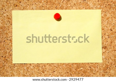 A yellow note held on a cork notice board with a red push-pin.