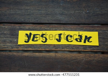 "A yellow note with a"" yes i can "" word on it on a wooden table"
