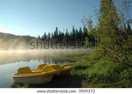 A yellow paddle boat is docked on the shore of a mountain lake in the early morning light.