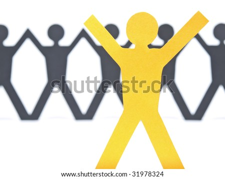 A yellow paper figure raising his arms. A paper man chain against the white background. Selective focus on the foreground. - stock photo