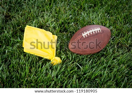 A yellow penalty flag and football lie motionless on a playing field. - stock photo