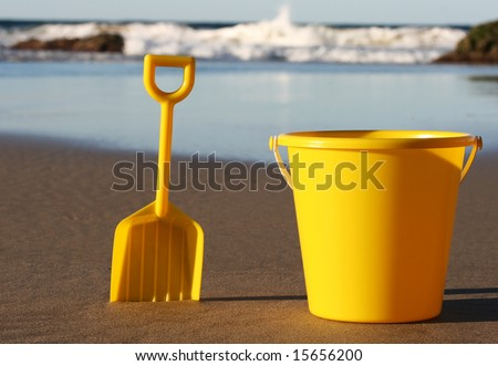 A yellow plastic bucket and spade on the beach, with the waves rolling in - stock photo