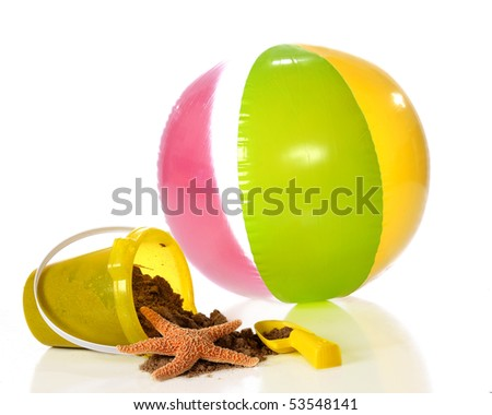 A yellow, plastic pail spilling wet sand and a starfish.  A colorful beach ball and shovel nearby.  Isolated on white. - stock photo