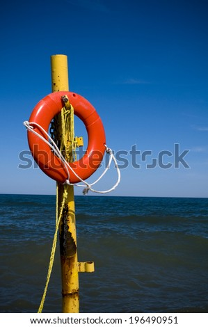 A yellow pole is holding a lifesaver on a beach. - stock photo