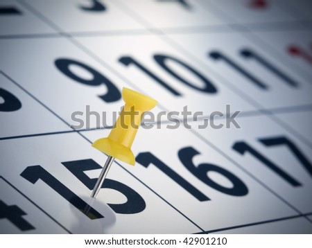 A yellow push pin on the 15th day of a calendar. - stock photo
