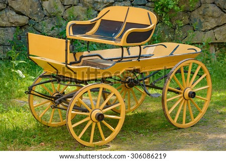 A yellow, renovated horse wagon with black details. Standing on grass in front of a stone wall. - stock photo