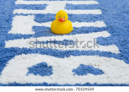 A yellow rubber duck on a bathmat that says bath. - stock photo