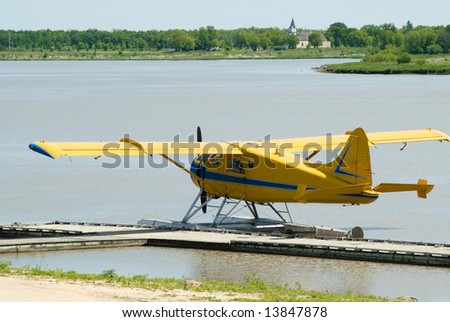 A yellow seaplane docked on the river during the day - stock photo