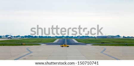 A yellow servicing truck moving on the middle of airport runway - stock photo
