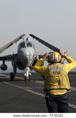 "A ""Yellow Shirt"" Aircraft Director Taxis an EA-6B Prowler Aboard a Nuclear Aircraft Carrier - stock photo"