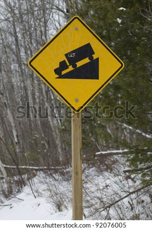 A yellow square or diamond steep hill truck incline sign against a winter forest.