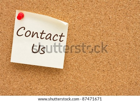 A yellow sticky note on a cork board with the words Contact Us on it