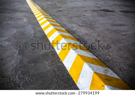 A yellow stripe speed ramp on concrete road. - stock photo