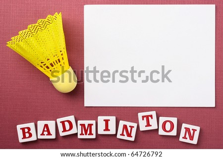 A yellow synthetic badminton shuttlecock next to a white piece of paper to which you can add your text.