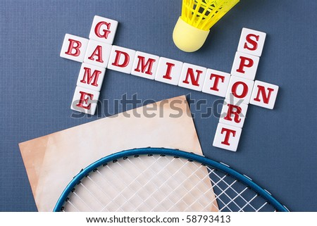 A yellow synthetic shuttlecock and a blue badminton racquet next to a badminton crossword.