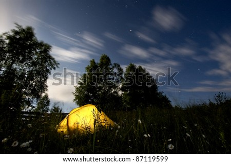 A yellow tent in mountains, in the middle of the night and the wind moving the trees and clouds - stock photo