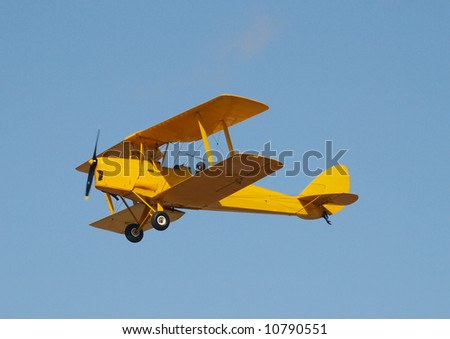 A yellow tiger moth flying in a blue sky - stock photo