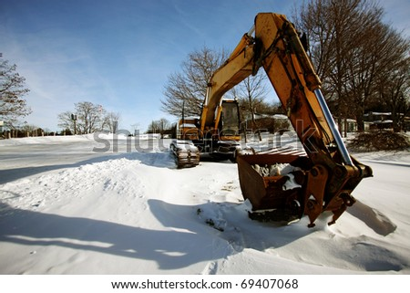 a yellow tractor in the snow - stock photo