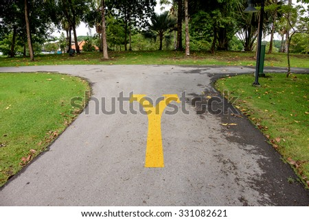 A yellow traffic arrow signage on an asphalt road indicating a detour left or right turn. - stock photo