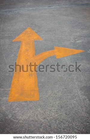 A yellow traffic arrow signage on the road - stock photo
