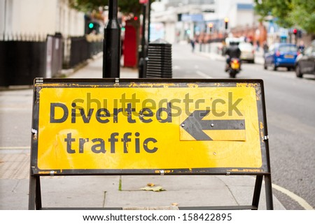 A yellow traffic diversion road sign with an arrow pointing left - stock photo