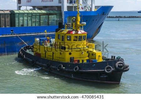 A yellow tugboat assisting a large cargo ship