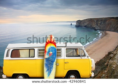 A yellow van with a surf board at the beach - stock photo