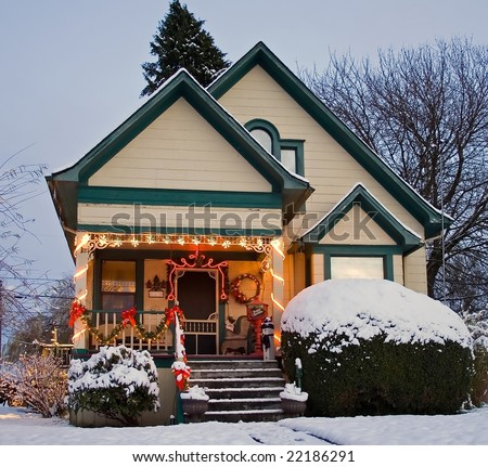 A Yellow Victorian house with green trim and Christmas Holiday Decorations. - stock photo
