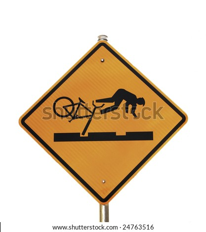 A yellow warning sign shows a bicyclist falling after their bike tire falls into a rut in the road. - stock photo