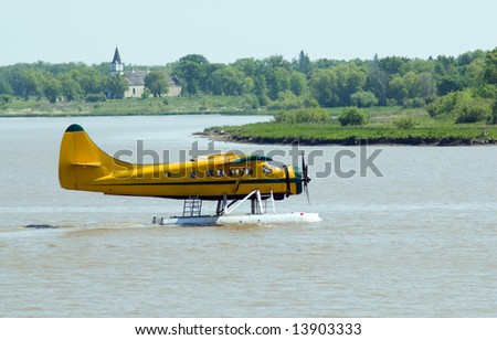 A yellow water planet floating on the river, preparing for take-off - stock photo