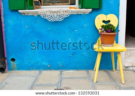 A yellow wooden chair placing in front of a bright blue house on Burano island, Italy - stock photo