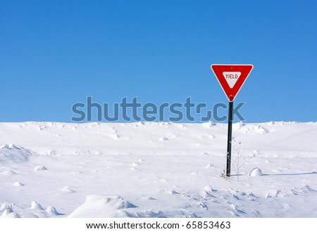 A yield sign sending a message in the middle of a very snowy winter. - stock photo