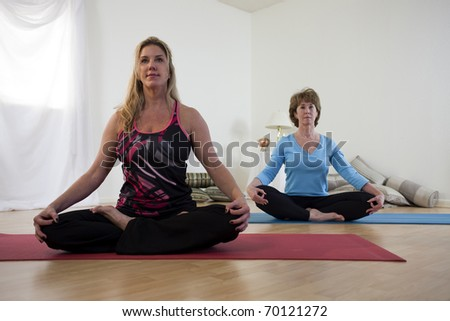 A yoga instructor and her student seated crossed leg on their mats in a small studio prepare for yoga practice.