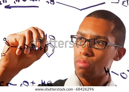 A yong man works on a chemistry problem. - stock photo