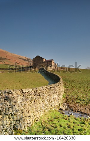 A Yorkshire Dales dry stone  wall leading to a stone barn - stock photo