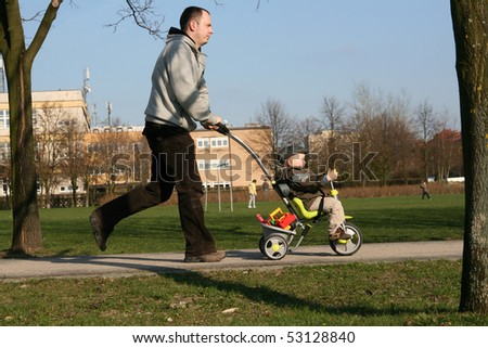 A young active family walking, running and playing at a park. Father is pushing tricycle. - stock photo