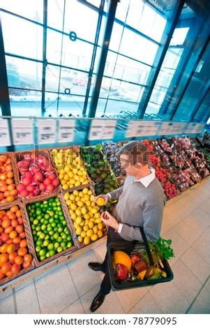 A young adult male buying fruits and vegetables in a supermarket - stock photo