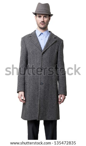 A young adult man dressed in a gray overcoat and a gray hat 1930's style, looking straight to the camera with plain face and hands besides his body. Isolated on white background. - stock photo