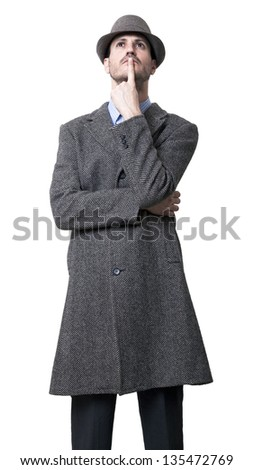 A young adult man dressed in a gray overcoat and a gray hat 1930's style, looking upwards with his finger on his lips, seems to be deep in thought. Isolated on white background. - stock photo