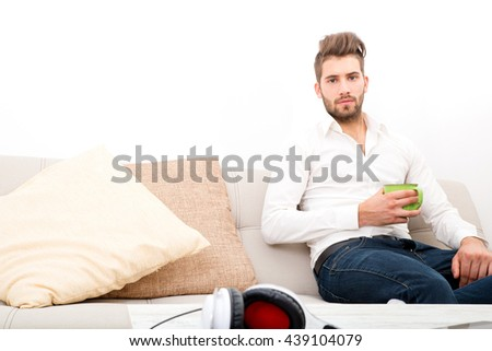 A young adult man sitting on the couch holding coffee. - stock photo