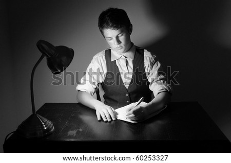 A young adult man writing a letter on a desk with a lamp. - stock photo