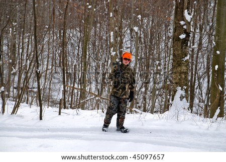A young adult out in the woods of a sporting clays course during the winter months in the snow. - stock photo