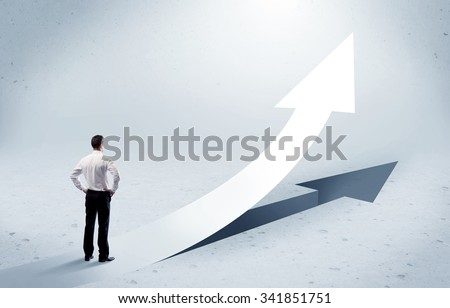 A young adult salesman standing in front of a big arrow pointing up with a shadow in grey empty space concept